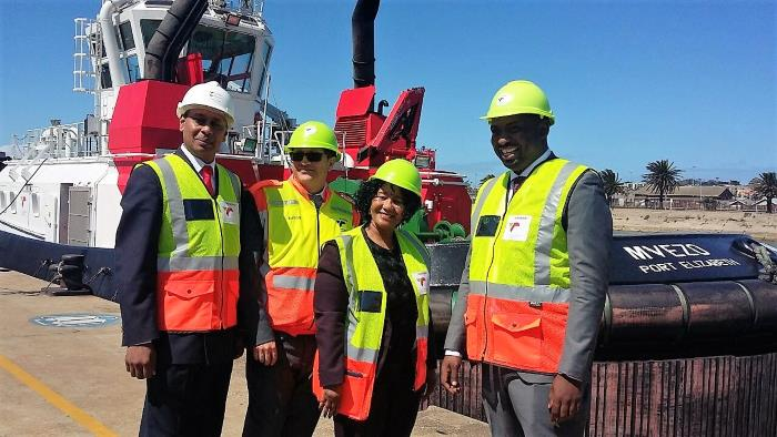 Ricky Bhikraj (TNPA's Research Executive & Operation Phakisa Programme Director), Rajesh Dana (PE Port Manager) and Tandi Lebakeng (Ngqura Port Manager) with Buti Manamela (far right). In the background is one of nine new 70-ton bollard pull tugboats built for TNPA by Southern African Shipyards in Durban, of which the Port of PE has two – MVEZO and QUNU, appearing in Africa PORTS & SHIPS maritime news