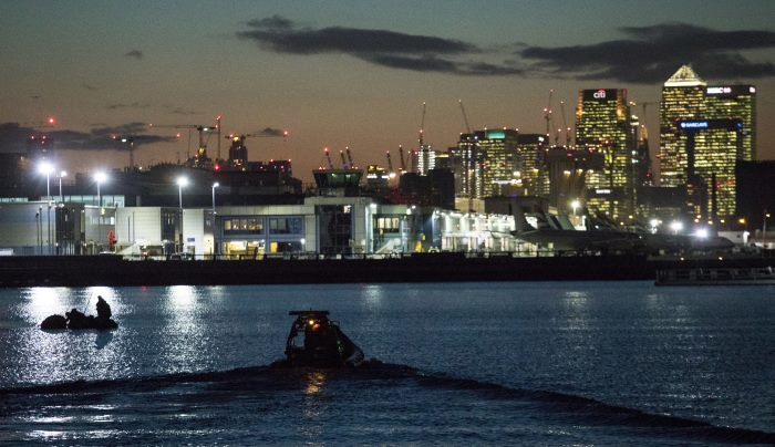 Image shows the divers lifting the bomb from the dock basin with a lifting bag visible. London's business centre skyline as a backdrop. The device was lying in a bed of dense silt and the first stage of the removal operation was to free the shell from the silt so it could be floated for removal. Timing of removal was dependent on tides. Picture: MoD Crown Copyright 2018 ©, featured in Africa PORTS & SHIPS maritime news