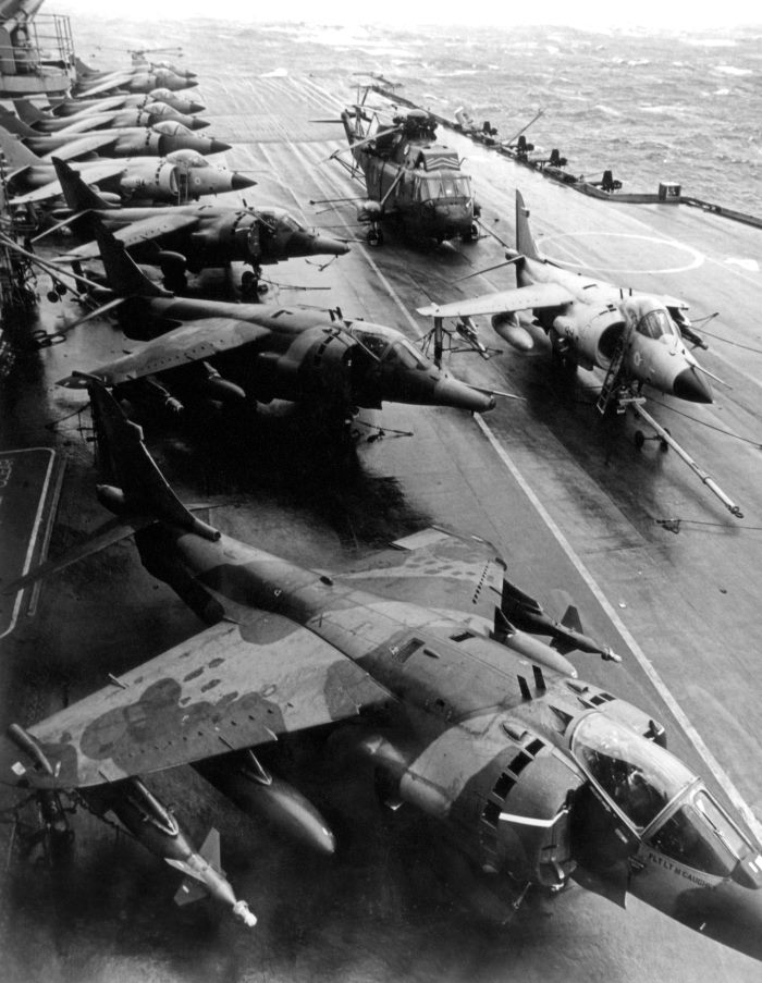 RAF 100 G Harrier GR.3 aircraft of 1 Squadron parked alongside Royal Navy Sea Harriers and a Sea King helicopter on the flight deck of HMS Hermes on 19 May 1982, the day that 1 Squadron joined with Hermes in the South Atlantic bound for the Falkland Islands. The Sea Harrier FRS.1 differed from the RAF's GR.3 in having extensive corrosion-proofing, a cockpit that was raised to provide the pilot with a better view, and a multi-mode radar called Blue Fox, which could search for targets in the air or on the surface. Photo: MOD Crown Copyright 2018 © from a story appearing in Africa PORTS & SHIPS maritime news