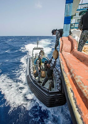 Leading Seaman Timothy Wilson passes down a bag of narcotics from the drug smuggling dhow to HMAS Warramunga's RIB. From a report in Africa PORTS & SHIPS maritime news