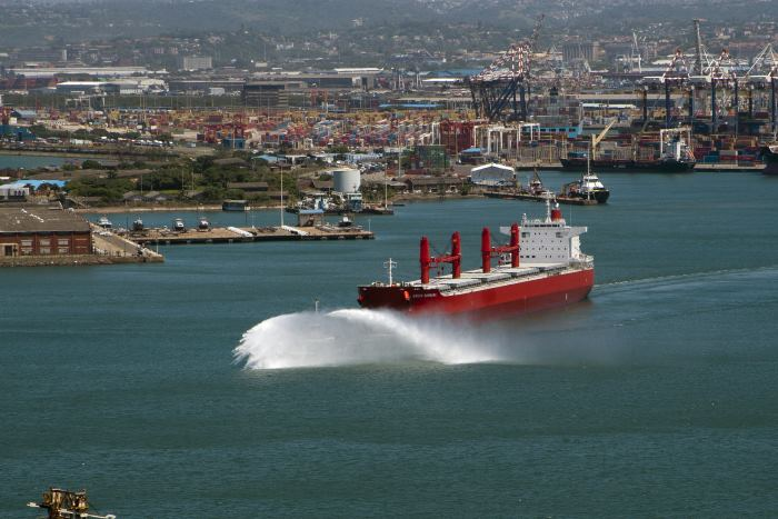 Island View Shipping's one-time charter vessel SANTA BARBARA makes her maiden departure from Durban in 2013, preceded by a display from one of the harbour tugs. Picture: Trevor & Debra Steenkamp, featured in Africa PORTS & SHIPS maritime news