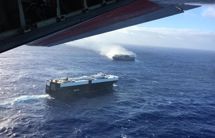 A Coast Guard HC-130 Hercules aircrew flies over the 650-foot Sincerity Ace on fire 1,800 nautical miles northwest of Oahu in the Pacific Ocean, Dec. 31, 2018, and drops supplies to the 944-foot bulk carrier Genco Augustus. Responders faced 17 to 20-foot seas, white caps, and significant winds making spotting survivors and rescuing them very difficult. (U.S. Coast Guard photo by HC-130 Hercules 1720/Released)