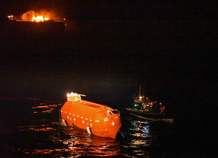 The rigid hull inflatable boat of HMS Argyll (right), pushed the lifeboat (left) of Grande America towards Argyll, as the cargo ship burned in the background, featured in Africa PORTS & SHIPS