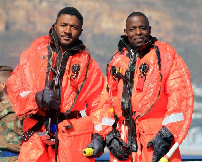 Chief Petty Officer Ayanda Mahlobo and Petty Officer Eric Luvhengo wearing the special escape suits, featured in Africa PORTS & SHIPS maritime news online