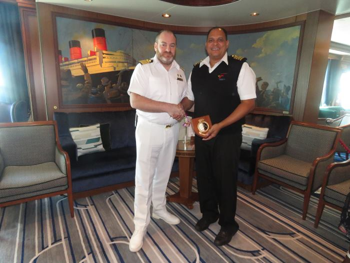 Captain Brynn Adamson (right) hands over a plaque to the captain of the vessel, Captain Tomas Connery