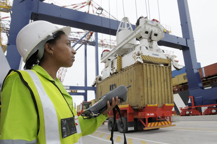 Standing under a Ship To Shore crane, a TPT youth employee processes containerized cargo for import and export using a Hand Held Terminal device at the Durban Container Terminal, featuing in Africa PORTS & SHIPS maritime news