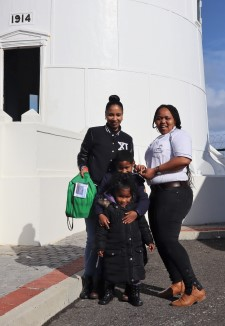 Local resident Maggy (left) was the lucky hundredth visitor to the Slangkoppunt Lighthouse on World Marine Aids to Navigation Day. Tembisa Niselo (right) from TNPA Lighthouse and Navigational Systems handed over a goodie bag to Maggy and her children Zayn and Zahra, fgeaturing in Africa PORTS & SHIPS maritime news