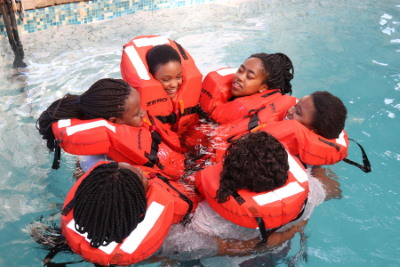 Learners [with faces visible], from left, Thimna Katikati, Mihlali Mfana, Masibulele Rixana and Anelisa Sani practice the buddy position to stay together and await rescue after abandoning ship. Picture: Sinomtha Gede, featured in Africa PORTS & SHIPS maritime news