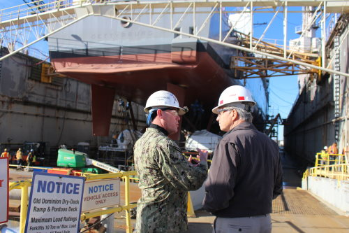 191218-N-KH778-4282 NORFOLK (Dec. 18, 2019) Capt. Corey Keniston, commanding officer of the Ticonderoga-class guided-missile cruiser USS Gettysburg (CG 64), discusses the dry docking availability for the ship with Secretary of the Navy for Manpower and Reserve Affairs Gregory Slavonic at the Old Dominion Dry Dock at BAE Systems shipyard in Norfolk, Va. Gettysburg is currently undergoing upgrades as part of the Navy's Service Life Extension Program for cruisers and landing support dock ships. (U.S. Navy photo by Lt. Mckensey Cobb/Released)