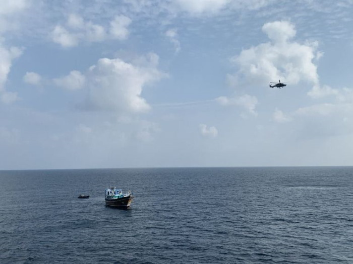 With the navy ship's helicopter overhead the dhow is approached, featured in Africa PORTS & SHIPS