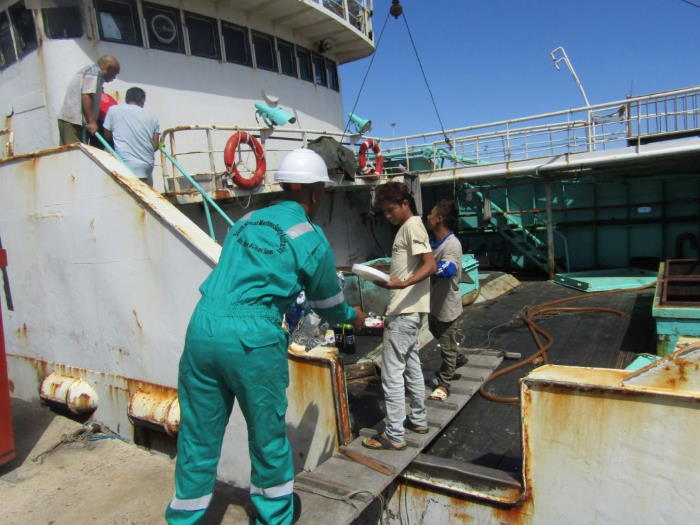 A Helping Hand: A SAMSA official hands over food items and related material to six crew members of a stranded vessel that entered South African sea waters and anchored off the port of Cape Town without permission a month ago. The vessel believed to be of Asian origin has since been quarantined and detained at the port of Cape Town pending resolution of its law transgressions since entering the country's waters illegally. Picture: SAMSA, featured in Africa PORTS & SHIPS maritime news