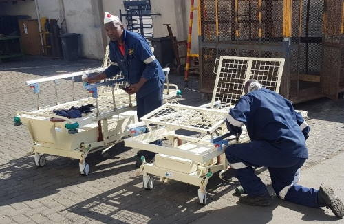 Members of Namdock's technical and fabrication teams working to refurbish hospital beds for Walvis Bay's state hospital, featured in Africa PORTS & SHIPS maritime news