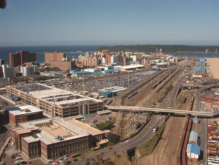 Durban Car Terminal, which includes the three-storey building at entre left, the open parking across the width of the picture, and an extensive parking staging area on the quayside. Picture: TPT, featured in Africa PORTS & SHIPS maritime news