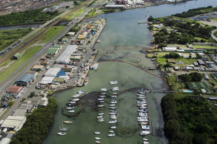 A view past the Bluff Yacht Club and Fish Wharf (at left) with the uMhlatuzane/uMbilo river mouth exiting into the Silt Canal at top left. The canal in turn empties to the right in the Bayhead region of Durban Bay and it was down the combined rivers (they join a short distance upstream) that the latest oil link occurred. Also to be seen at left with a bridge crossing the rivers is the notorious Bayhead Road, largely devoid of traffic on this occasion. This earlier scene was in 2015 and was photographed by one of Durban's top veteran photographers, Russell Cleaver, as featured in Africa PORTS & SHIPS maritime news